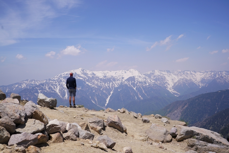 A man stands on a mountain summit looking out