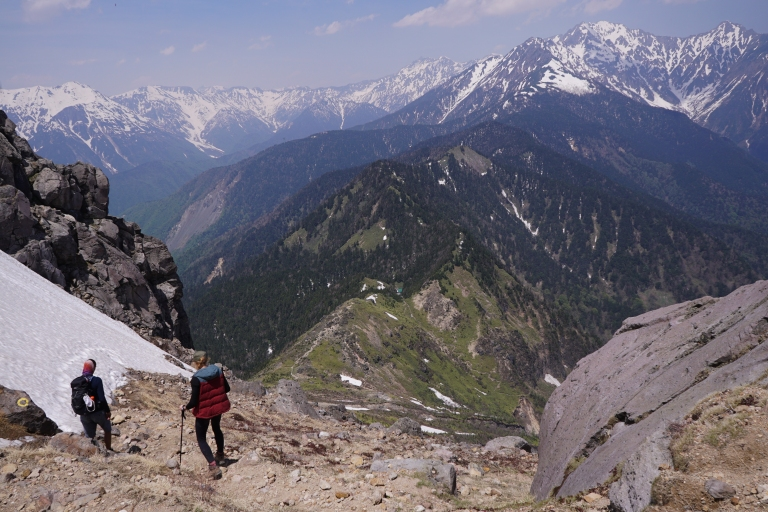 2 hikers walk down a rocky slope with mountains in the distance