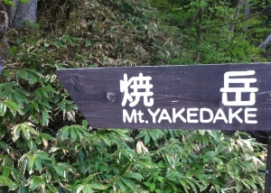 A wooden sign points left to Mt. Yakedake