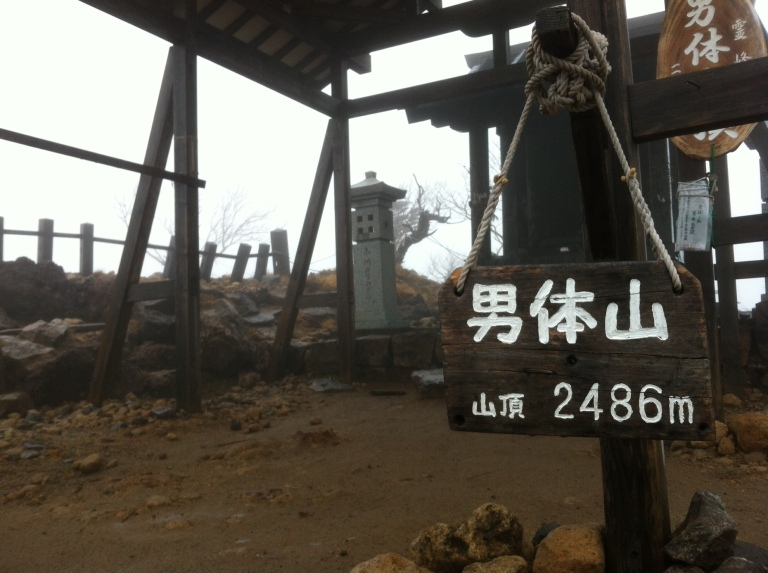 A sign reading 2486 m in front of a simple wooden shrine