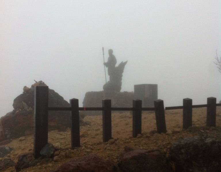 A statue behind a fence shrouded in mist
