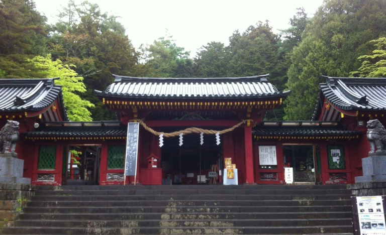 Black tiled shrine with red pillars and statues and stairs