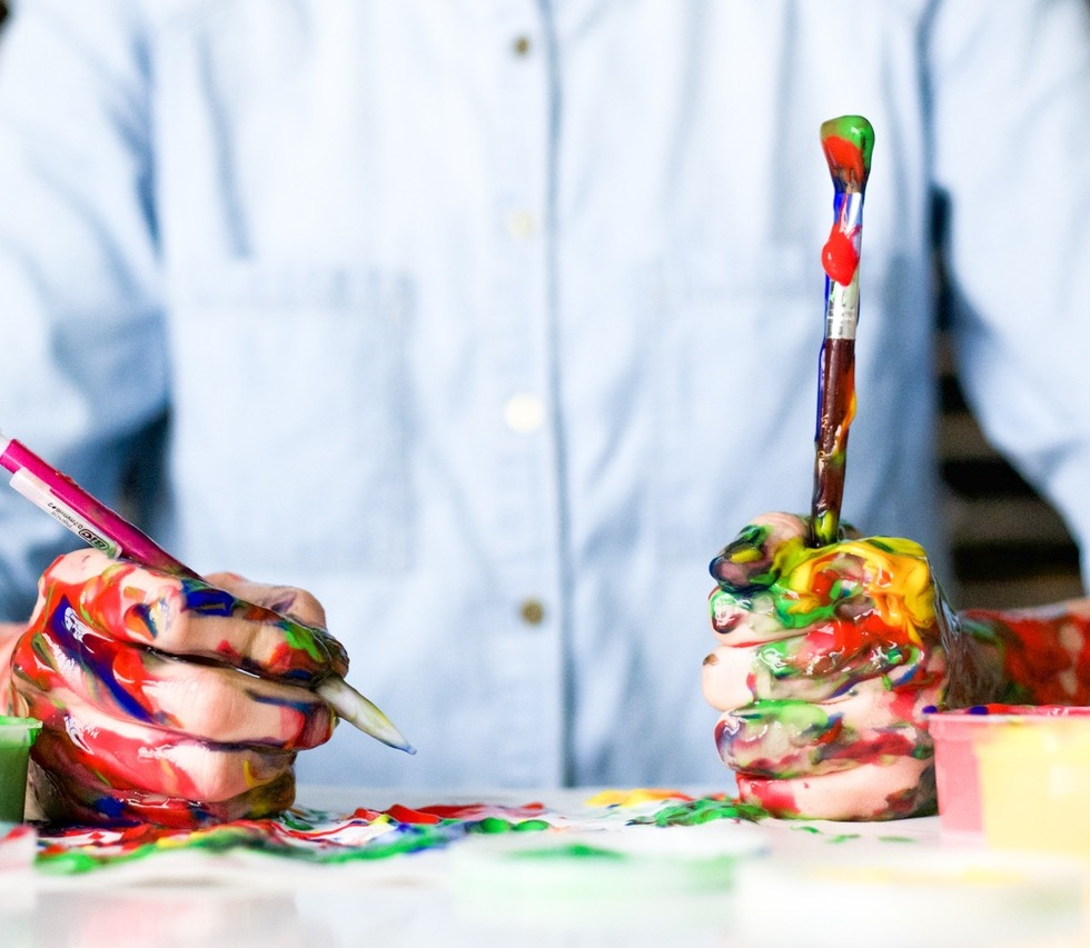 A man holds two paintbrushes in hands covered in paint