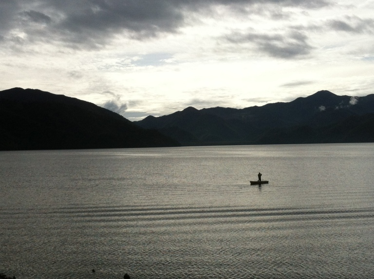 A lake with a single man in a rowing boat and hikks behind