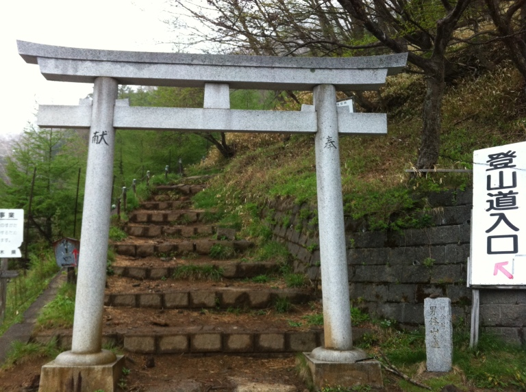 White gate with japanese inscriptions and stone steps behind