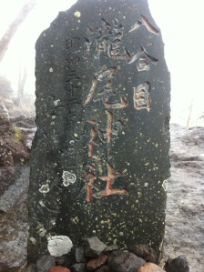 A grey standing stone with japanese inscriptions