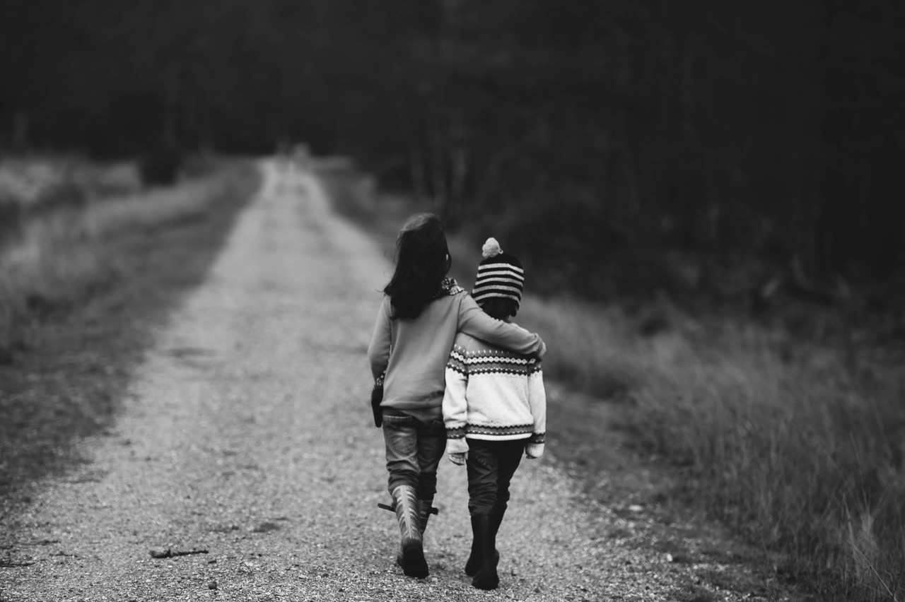 Two children walk away down a path arm in arm. Black and white image