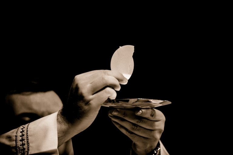 A priests hands hold up bread during the eucharist