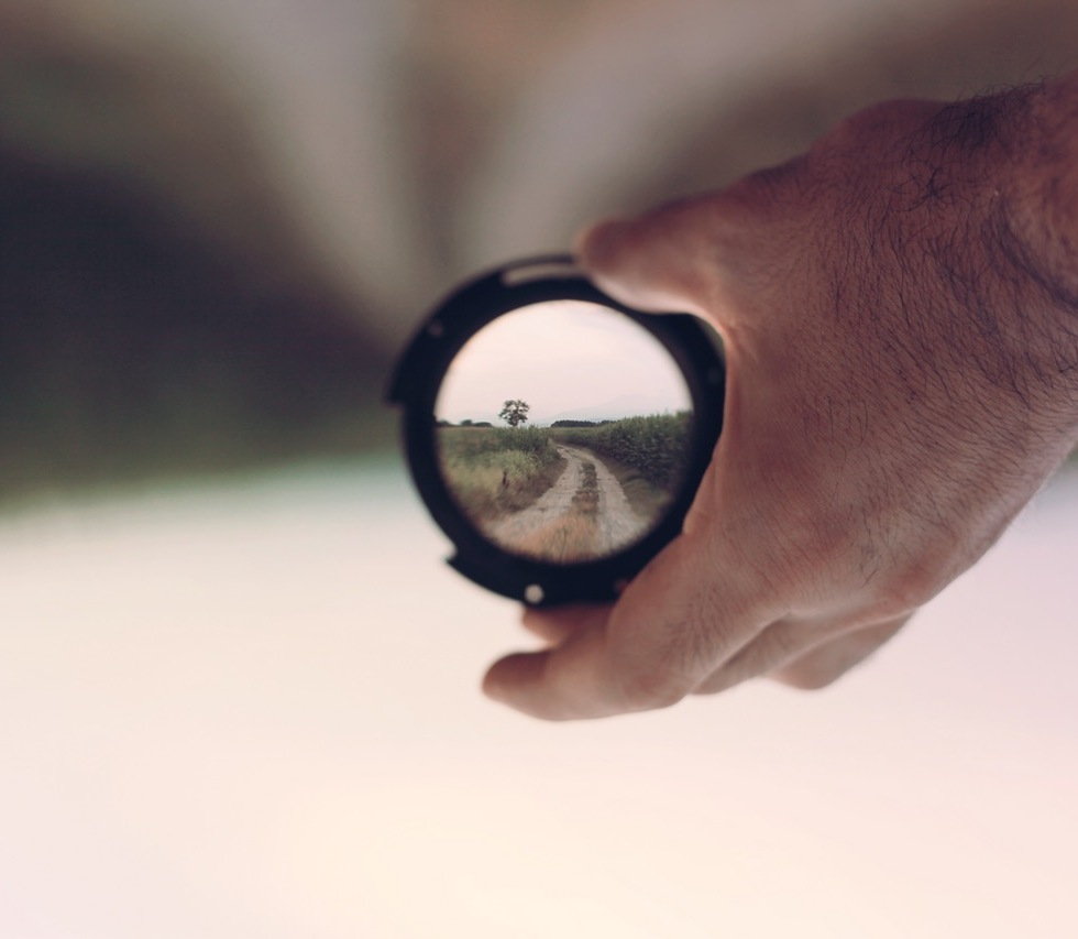 A magnifying glass focusses a blurred image of a path